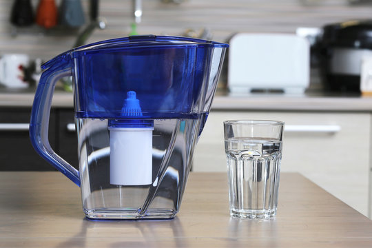 Glass of clean water and filter for cleaning drinking water on the table in the kitchen. Purification of drinking water at home.
