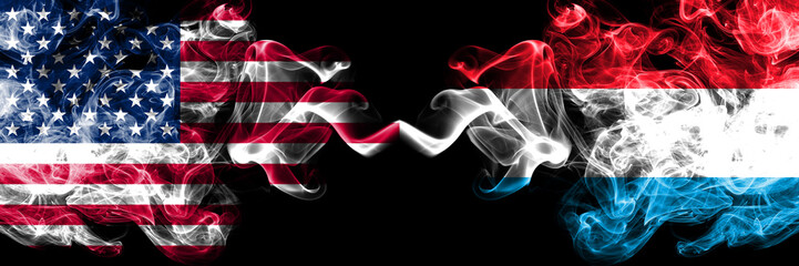 United States of America vs Luxembourg smoky mystic flags placed side by side. Thick colored silky smoke flags of America and Luxembourg