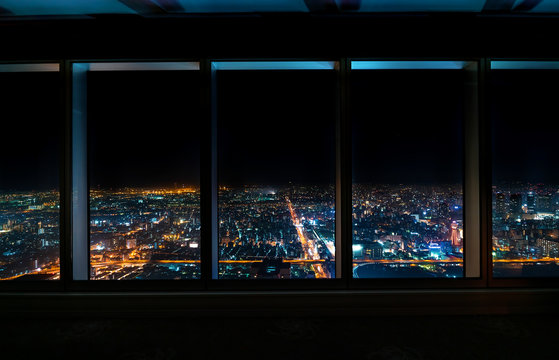 Aerial view of the Osaka skyline at night through a skyscraper window