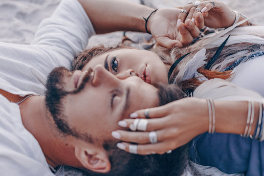 beautiful young couple lying on sand on the beach. love and relationships concept