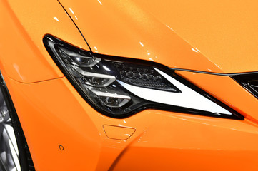 Wall Mural - Detail on one of the LED headlights orange car.