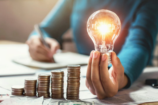business woman hand holding lightbulb with coins stack on desk. concept saving energy and money