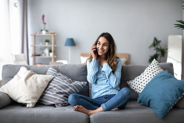 Smiling woman talking on the phone at home on the sofa. Wall mural