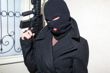 Young girl in black balaclava holding an assault rifle gun. Female terrorist fun concept