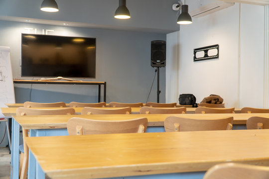 Small empty classroom or meeting room interior with modern wooden table, chairs and lamps. Learning media with television, audio and whiteboard.