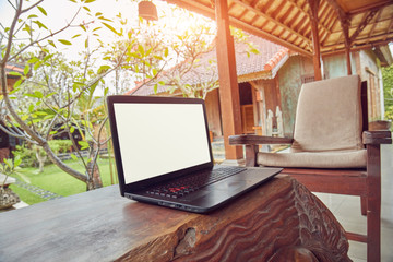 Laptop on a home porch / patio with view to a garden.