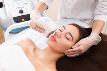 The procedure of photoepilation in the beauty salon. A young woman is removed unwanted hair on her face. Hardware cosmetology. Close up