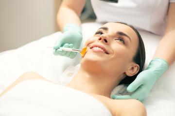 Fototapeta Young lady smiling while cosmetologist using peeling brush obraz