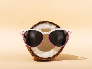 Half coconut in sunglasses on yellow background. The concept of relaxation, summer mood, copy space.