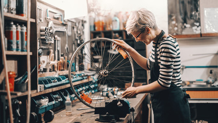 Cute Caucasian female worker holding and repairing bicycle wheel while standing in bicycle workshop. Fototapete