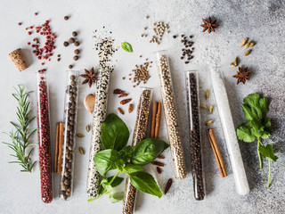 Fototapeta Various spices in glass test tubes and fresh herbs on gray background. Set of various spices and herbs flat lay obraz