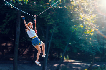 Happy women girl female gliding climbing in extreme road trolley zipline in forest on carabiner safety link on tree to tree top rope adventure park. Family weekend children kids activities concept Fototapete