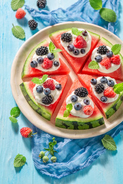 Homemade watermelon pizza with whipped cream and fresh berry fruits