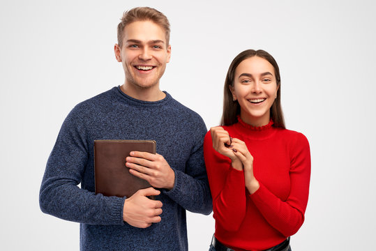 Cheerful friendly students, have fun together, hold brown notebook. Models stand over white background in studio