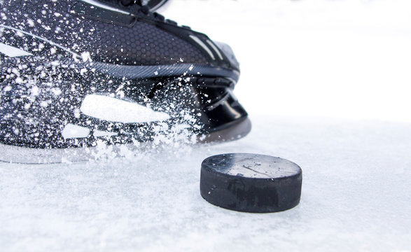 hockey skate with snow splashes and puck