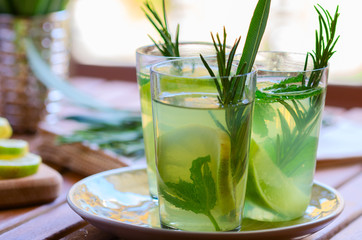 Three glasses with atural  lemonade made from  lemon rosemary and mint in glasses on wooden table at the terrace. Cold refreshing beverage for hot summer day.