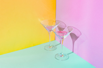 Two cocktail glasses with funny pink liquid. Strong fashion shadows. Concept of luxury relax with...