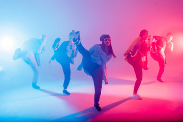 Group of diverse young hip-hop dancers in studio with special lighting effects in blue and pink colores Fotomurales
