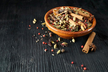 Ceramic bowl with mixed spices on wood background with copy space