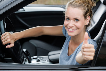 cute woman giving thumb up inside her car