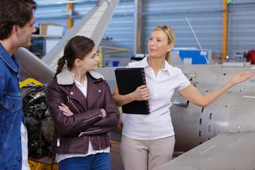 mature woman giving tour of aircraft hangar