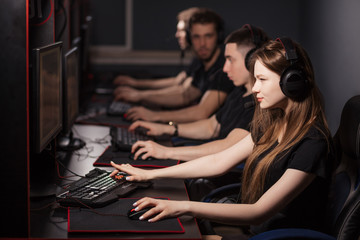 Team of professional eSport gamers with a cute young woman in focus playing in video Games on a Cyber Games Tournament. They using headsets and high-powered game computers.