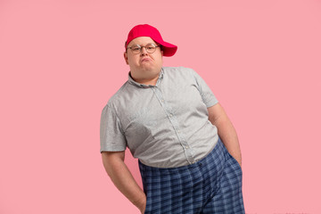 Obraz Comical home superhero with arrogant face wearing checkered huge shorts shows his muscles and competence isolated on pink background - fototapety do salonu