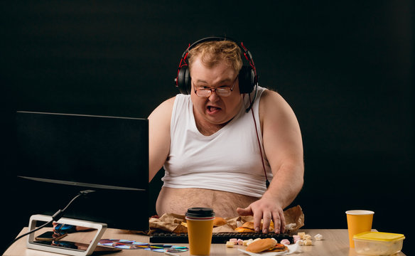 funny man is crazy about computer games and fast food. close up photo, isolated black background. studio shot.
