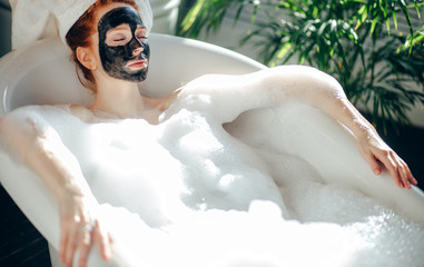 Skin care - Young lady with facial black clay mask applyed on her face relaxing in foam bath, getting rejuvenation spa and beaty procedure at home