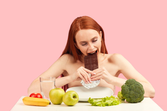 Hungry red-haired woman on a strict diet chooses to eat a chocolate bar instead of a healthy vegetables and fruits, feeling happiness and satisfaction from choice.