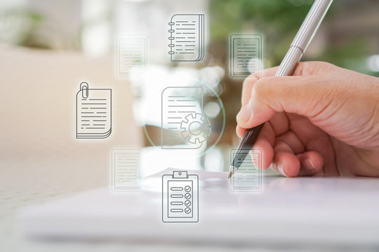 Document Report and business data system business HR technology Concept: Businessman Manager hands holding pen for checking and signing white documents reports papers of files icon in modern office