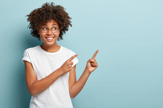 Studio shot of optimistic Afro American woman with crisp hair, positive smile, points aside with fore fingers, wears round spectacles and white t shirt, shows awesome thing at upper right corner