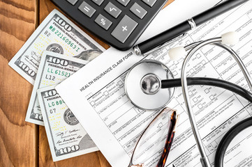 Health insurance claim form with money, calculator and stethoscope on the table. Top view.