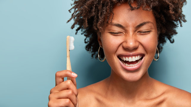 Dental health concept. Happy smiling dark skinned woman with curly hair, laughs while has morning routines, shows bright smile, holds toothbrush, stands with bare shoulders over blue background