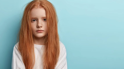 Small cute child with serious sad expression, long red hair, freckled skin, has natural beauty, listens carefully to parents, makes decision, models over blue wall with empty space on right side