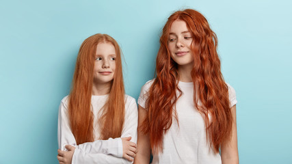 Ginger family. Redhead beautiful sisters with freckled skin, gentle smiles, look at each other, cant decide who should tell secret to parents first, wear white casual clothes, has similar appearance.