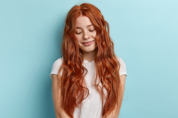 Indoor shot of timid ginger teenage girl looks down with dreamy pleased thoughtful expression and tender smile has long wavy foxy hair, dressed in casual white t shirt, isolated on blue background