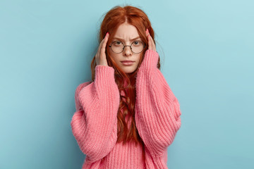 Unhappy red haired girl touches temples, feels headache after working long hours, has gloomy facial expression, dressed in pink knitted jumper, needs painkillers, isolated on blue studio wall