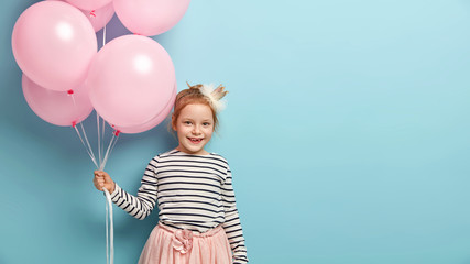 Funny attractive female kid goes on birthday party, carries pink air balloons, wears striped jumper, skirt and crown on head, smiles broadly, has lack of teeth, isolated on blue wall, empty space