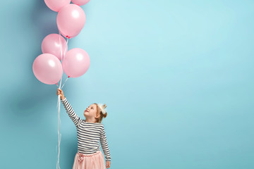 Happy kids carnival. Little princess holds rosy balloons, smiles joyfully, wears striped jumper and long skirt, expresses true positive emotions, celebrates something, isolated over blue background
