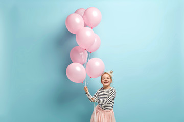 Positive small kid dressed in festive clothes, carries air balloons, celebrates holiday, has broad smile, stands against blue background, being in high spirit. Children and celebration concept