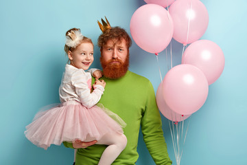 Candid shot of redhead father holds on hands small daughter who wears crown, white jumper and tulle skirt, looks curiously happily at dad, asks for whom these balloons. Children day celebration
