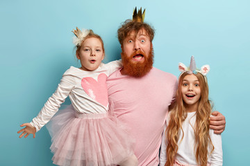 Foxy bearded father stands between two little daughters, embraces and has surprised look, celebrate International Children Day. Impressed dad and two girls with unicorn horn and crowns on heads