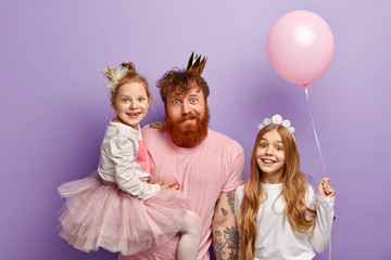 Photo of caring affectionate father plays with small daughters, organizes party for children, wear crowns, dressed in fashionable clothes, isolated over purple background. Family and fun concept