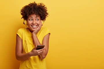 Joyful black woman with toothy smile, listens popular song via headphones, holds modern cell phone, likes listening music during spare time, isolated over yellow background. Teenagers and technology