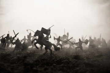 Medieval battle scene with cavalry and infantry. Silhouettes of figures as separate objects, fight between warriors on sunset foggy background. Selective focus Wall mural