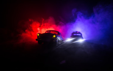 Police car chasing a car at night with fog background. 911 Emergency response police car speeding to scene of crime. Selective focus - fototapety na wymiar