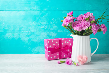 Mother's day background with flowers, heart shape and gift box on wooden table