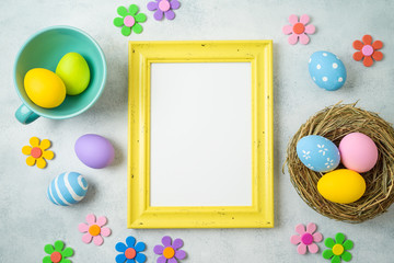 Easter holiday background with easter eggs and photo frame on table.