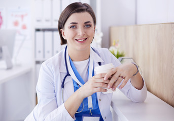 Portrait of professional female doctor holding cup of coffee